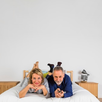 Aged happy woman and man with tv remote watching tv on bed