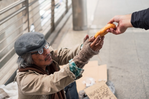 Aged homeless beggar reach out to get bread on donor hand at corridor bridge