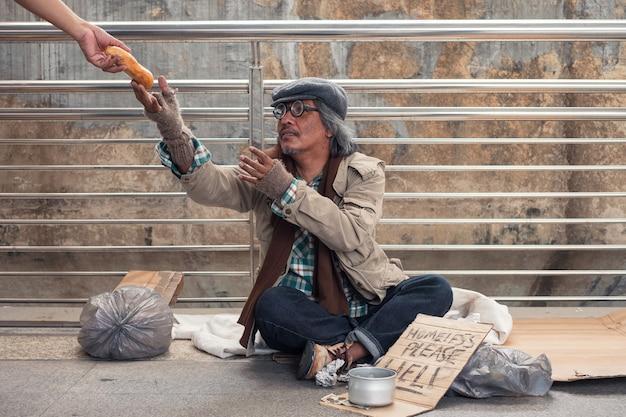 高齢のホームレスの乞食が廊下の橋で寄付者の手にパンを手に入れるために手を差し伸べる