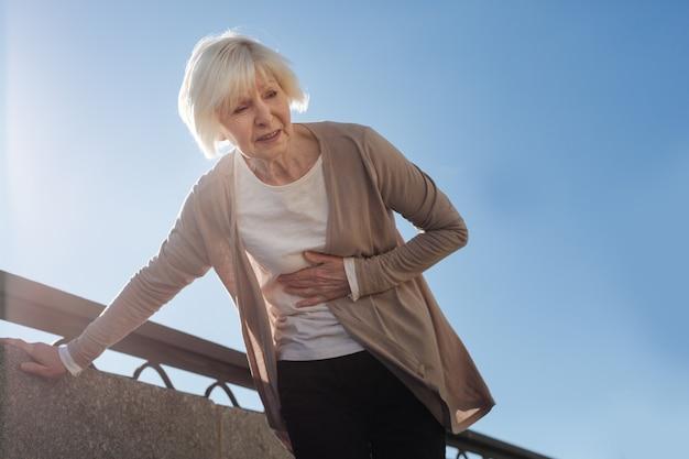 Пожилая больная испуганная женщина стоит и чувствует ужасную боль в животе во время прогулки по набережной