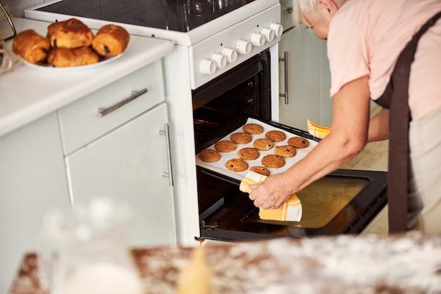 オーブンからクッキーとベーキングシートを取得する老婦人