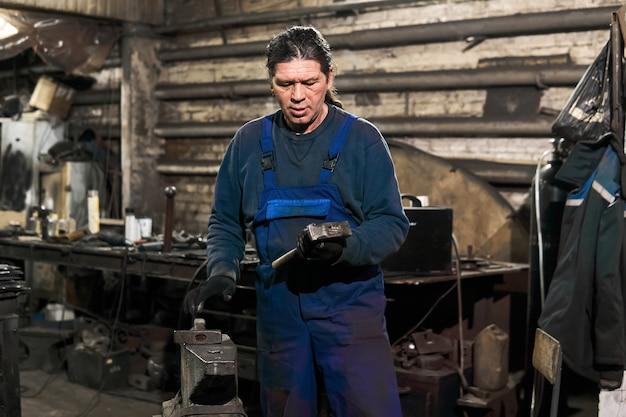 年配の男性の鍛冶屋は、仕事の準備をしているワークショップで働き始めるためにハンマーを選びます