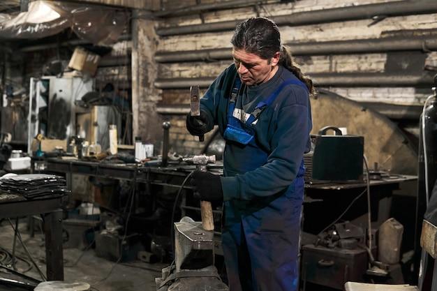 年配の男性の鍛冶屋は、仕事の準備をしているワークショップでハンマーをまっすぐにします