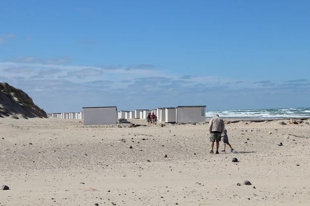 Aged male and his grandson walking in the seaside camp at lokken, denmark