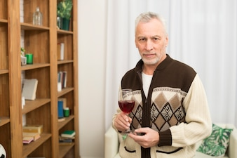 Aged male with glass of wine near bookshelves in room