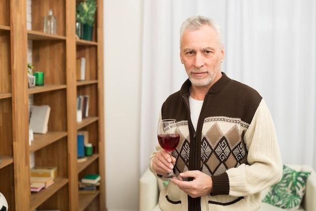 Maschio invecchiato con bicchiere di vino vicino a scaffali in camera