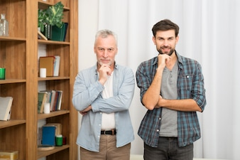 Aged man and young guy with hands near chins in room