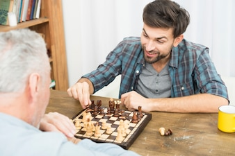 Aged man and young happy guy playing chess at table in room