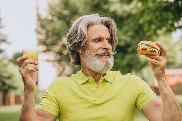 Пожилой мужчина, выбирая между гамбургером и яблоком
