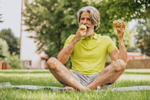 Uomo invecchiato che sceglie tra hamburger e mela