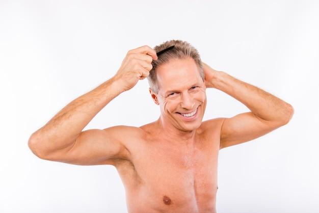 Пожилой мужчина расчесывает волосы