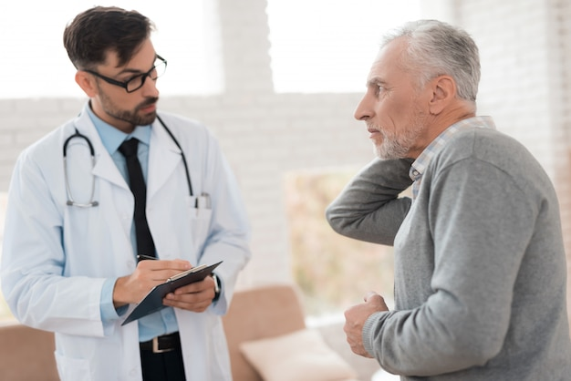 노인은 목에 통증이 있다고 의사에게 불평합니다. 프리미엄 사진