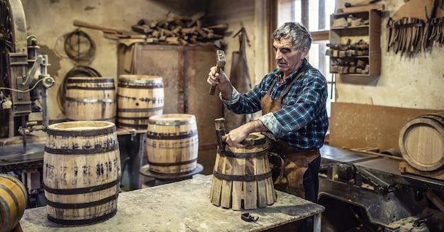 나이든 남자는 망치를 사용하여 나무 조각 주위에 금속 고리를 놓는 새로운 빈티지 모양의 나무 통을 만듭니다.