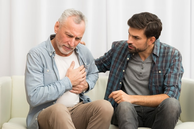 Aged man having heart attack near young guy on sofa