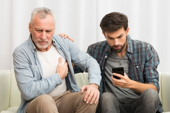 Aged man having heart attack near young guy using smartphone on sofa