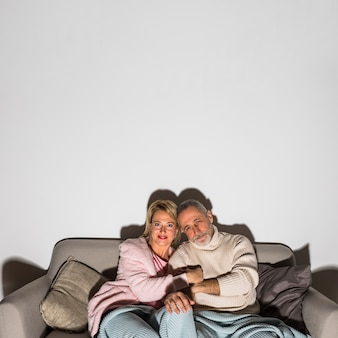 Aged man holding hands with woman and watching tv on settee