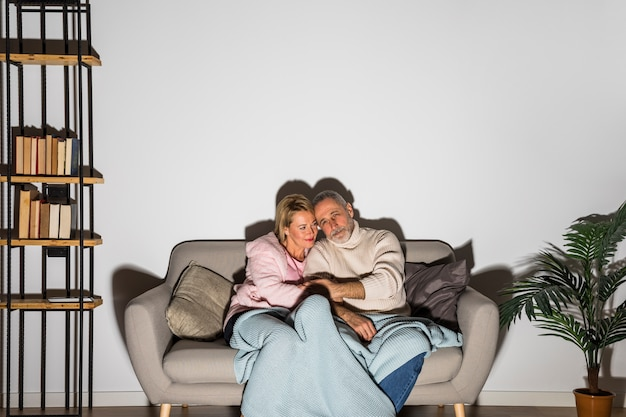 Aged man holding hands with woman and watching tv on sofa