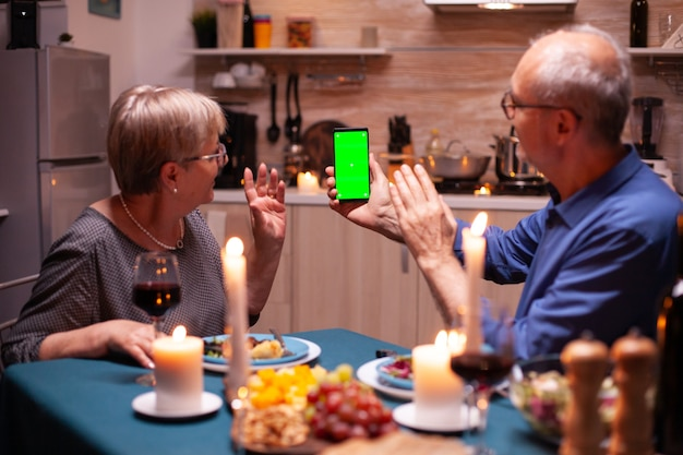 Aged man holding phone with green screen and wife is waving at it. aged people looking at mockup template chroma key isolated smart phone display using techology internet sitting at the table