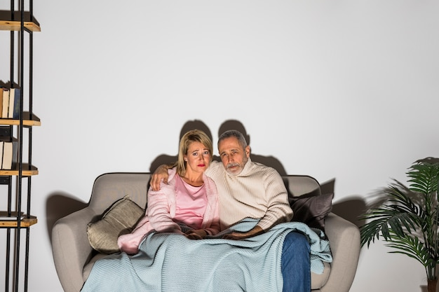 Aged man hugging woman and watching tv on sofa