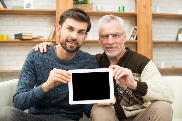 Aged man hugging young guy and showing tablet on settee