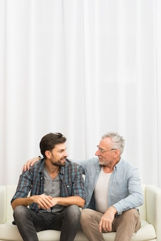 Aged man hugging young guy on sofa