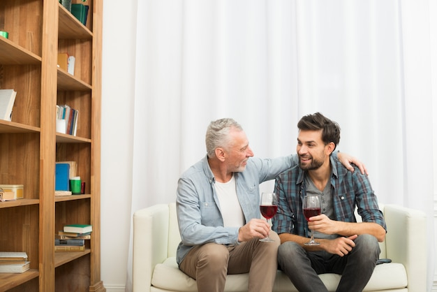 Aged man hugging young smiling guy with glasses of wine on sofa in room