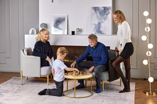 나이든 남자는 가족의 저녁 시간에 손자와 체스를 하고 있다