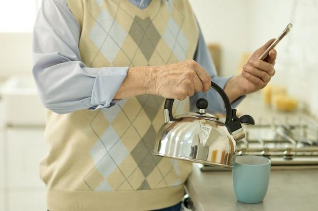 Пожилой мужчина смотрит и смартфон и наливает воду из чайника