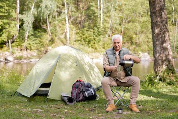 Пожилой мужчина наливает горячий чай или воду в чашку, сидя на небольшом дорожном кресле у туристической палатки в лесу