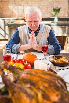 Aged man praying at table