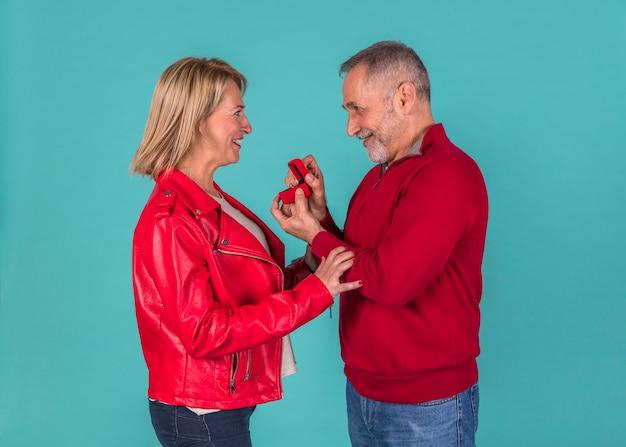 Aged man presenting jewellery box to amazed woman