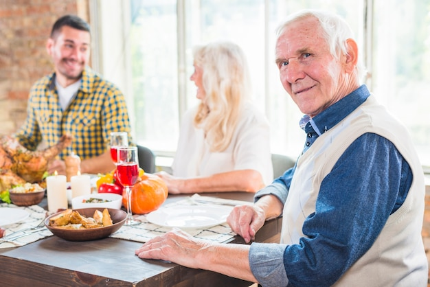 Aged man sitting at table near grey woman and young male