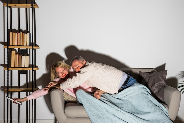Aged man stopping smiling woman with tv remote to change channel on tv on sofa