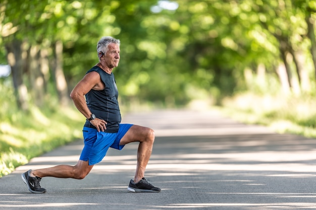 Aged man stretches legs outdoors surrounded by trees before his workout.