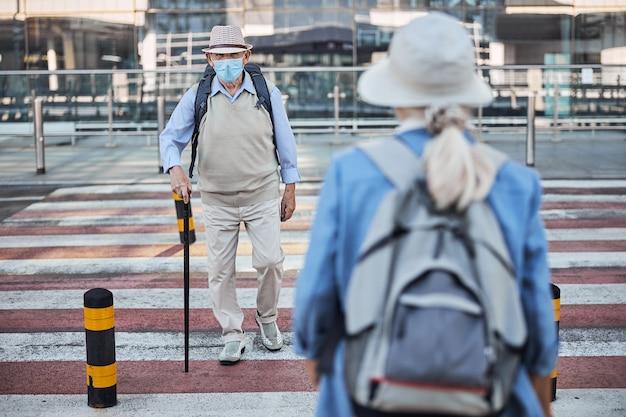 걷는 지팡이를 든 세 남자와 서로를 지나가는 배낭을 든 여자