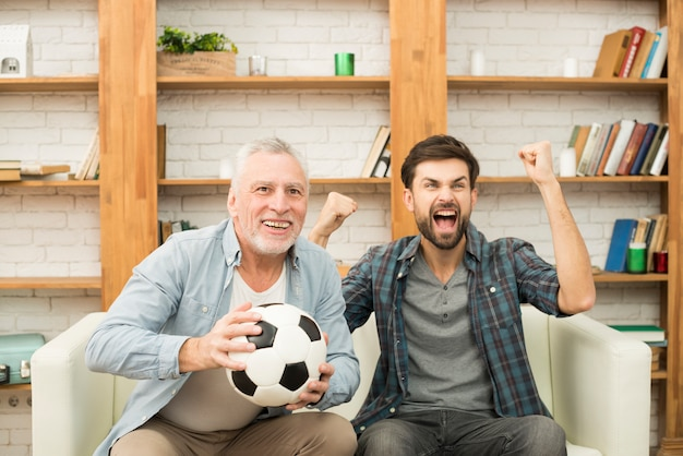 Aged man with ball and young crying guy watching tv on sofa