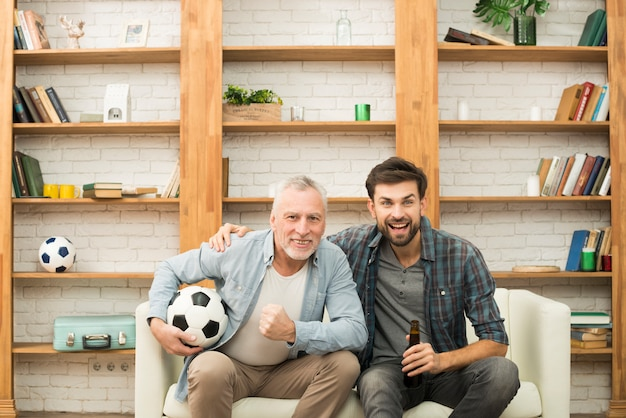 Aged man with ball and young guy with bottle watching tv on sofa