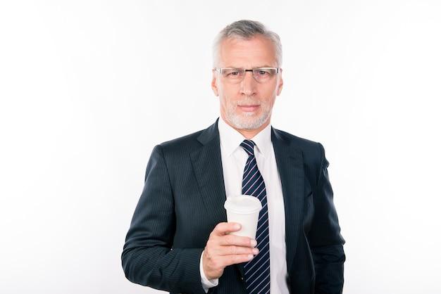 Пожилой мужчина в очках в черном костюме держит чашку кофе