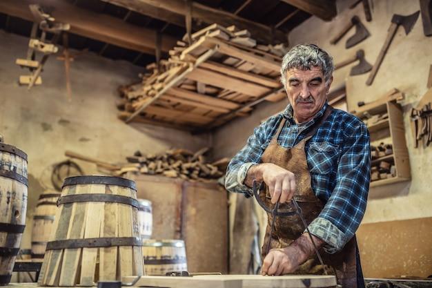 회색 머리를 한 노인은 오래된 작업장에서 목공 일을 합니다.