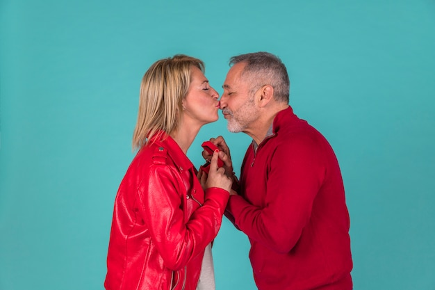 Aged man with jewellery box kissing with woman