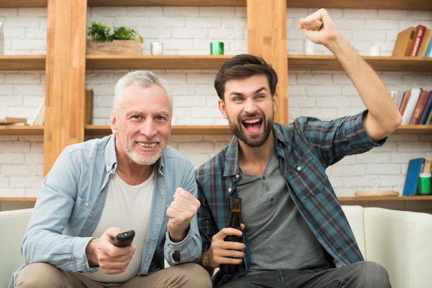 Aged man with remote control and young crying guy with bottle watching tv on sofa
