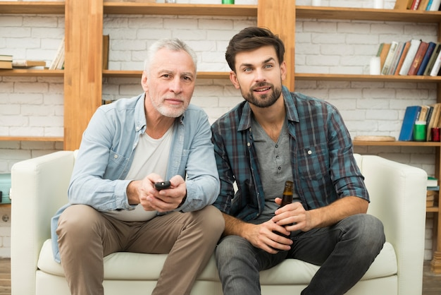 Aged man with remote control and young guy with bottle watching tv on sofa