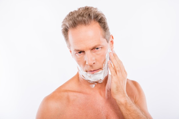 Пожилой мужчина с пеной для бритья на подбородке