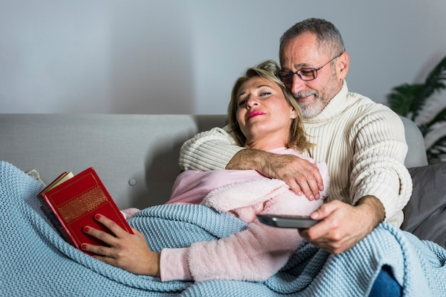 Aged man with tv remote embracing woman with book on sofa