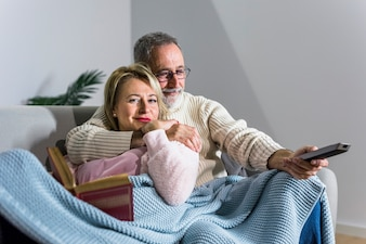 Aged man with TV remote watching TV and smiling woman with book on sofa