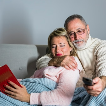 Aged man with tv remote watching tv and cheerful woman with book on sofa