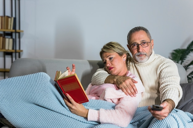 Aged man with tv remote watching tv and woman reading book on settee