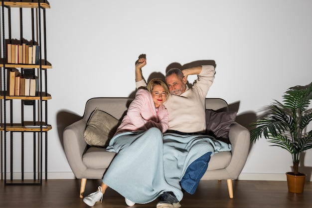 Aged man with upped hands near smiling woman watching tv on sofa