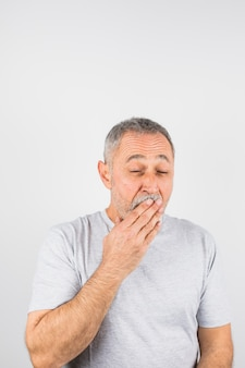 Aged man yawning covering  his mouth
