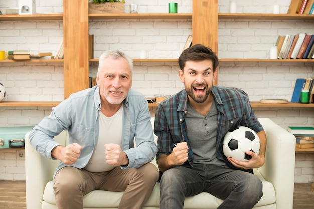 Aged man and young crying guy with ball watching tv on sofa